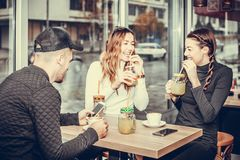 Young man and two women sitting at the table in the cafe shop. Cheerful group of friends, one men and two women sitting at the table in the cafe shop,  talking Stock Images