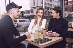 Young man and two women sitting  in the cafe shop. Cheerful group of friends, one men and two women sitting at the table in the cafe shop,  talking and having Stock Images