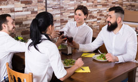 Cheerful group of friends at restaurant table Stock Photos