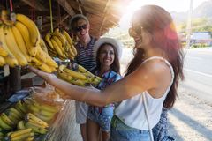 Cheerful Group Of People Buying Bananas On Street Market Young Tourists Communicating While Shopping Fruits In Asian. Bazaar Concept Stock Photo