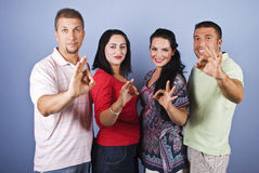 Cheerful group people show okay signs. Cheerful group of people friends standing in a line and showing okay signs on blue background,check also royalty free stock photography