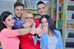 Cheerful group of students smiling at camera with thumbs up, success and learning concept Stock Image