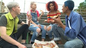 Cheerful group of teenagers enjoying rest eating pizza outdoors having fun