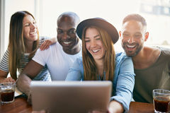 Cheerful group of young co-workers sharing tablet. Four smiling young people sitting at table and having fun while sharing something on tablet in office Stock Photos