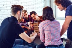 A cheerful group of young people play board games. A cheerful group of young people play board games in the room Stock Photography