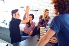 A cheerful group of young people play board games. A cheerful group of young people play board games in the room Stock Image