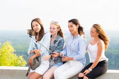 Cheerful group of young smiling women makes a selfie using a selfie stick royalty free stock images