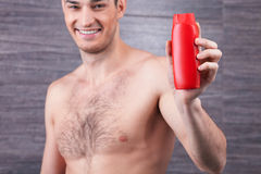 Cheerful guy is advertising hair care product royalty free stock image