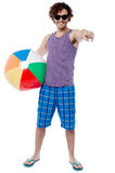 Cheerful guy with beach ball pointing at you. Relaxed young man with beach ball enjoying vacation Stock Photo
