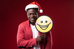 Cheerful guy with closed eyes holding emoji. Having fun. Joyful man in santa hat standing with carton icon of smiling face. Isolated on red background royalty free stock images
