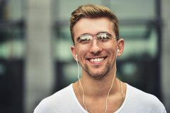 Cheerful guy dressed in white t-shirt at the street, listening to music with earphones, holding mobile phone. royalty free stock images