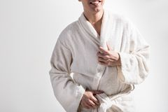 Cheerful guy in dressing gown is smiling. Good start of day. Close up of torso of optimistic young man in white terry cloth bathrobe is standing against light stock photo