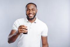 Cheerful guy drinking tasty beverage Stock Photos