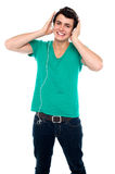 Cheerful guy enjoying loud music. Holding them tightly to ears Royalty Free Stock Photos