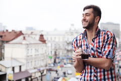 Cheerful guy is feasting his eyes upon town stock photo