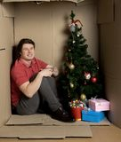 Cheerful guy is feeling happiness inside cramped carton box. Waiting for new year concept. Full length portrait of optimistic young man is sitting on floor ine royalty free stock photography