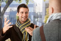 Cheerful guy gesturing to friend Stock Photos