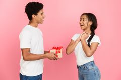 Cheerful guy giving his girlfriend present in studio. Cheerful guy giving his girlfriend present over pink background stock photo