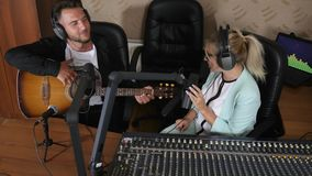 Cheerful guy in headset playing on musical instrument next to radio presenter near audio console in room. Cheerful guy in headset playing on musical instrument stock footage
