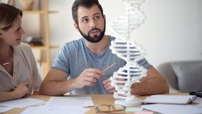 Cheerful guy helping his female groupmate with genetics study