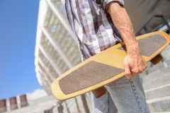 Cheerful guy holding his skate. Close up of young man carrying skateboard. He is walking down stairs Stock Photo