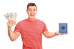 Cheerful guy holding money and a small safe Royalty Free Stock Photography