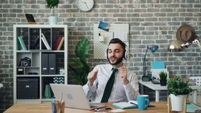 Cheerful guy listening to music singing dancing at work using headphones