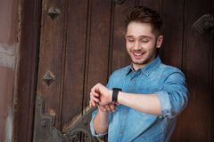 Cheerful guy looking at his wrist watch Stock Photography