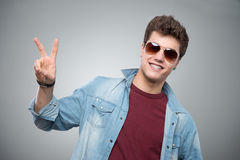 Cheerful guy making victory sign Royalty Free Stock Images
