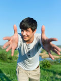 Cheerful guy with outstretched arms outdoors Stock Images