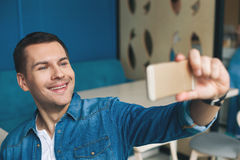Cheerful guy is photographing himself on telephone Stock Photos