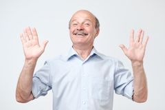 Cheerful guy raises hands as shows being uninvolved, has happy look royalty free stock images