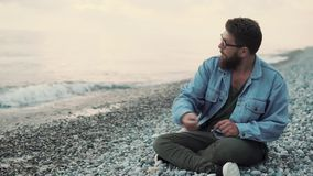Bearded man is throwing stones into water of sea, sitting in shore in evening. Cheerful guy is relaxing on beach in twilight and throwing pebbles in water. He is stock video footage