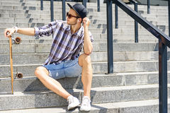 Cheerful guy with resting skateboard on steps. Cool young man is sitting on stairs and holding skate. He is listening to music from earphones with pleasure and Stock Photography