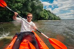 Cheerful guy sits in red kayak and row with a paddle royalty free stock photography