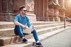 Cheerful guy sitting on the footsteps. Live life bright. Cheerful content smiling man holding tablet and expressing gladness while sitting on the footsteps stock photography