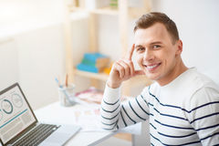 Cheerful guy sitting at the table. Gladness in mind. Cheerful positive smiling handsome man sitting at the table and working on the laptop while expressing joy royalty free stock photo