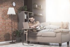 Cheerful guy with stubble is typing on notebook stock photo