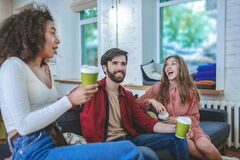 Cheerful guy and two girls on sides sitting on couch