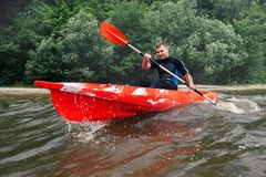 Cheerful guy in wetsuit sits in a red kayak and row with a pad stock photos