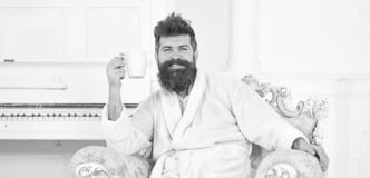 Cheerful guy in white bathrobe enjoying morning coffee. Bearded man sitting in beautiful antique armchair. Energetic. Morning at home royalty free stock photos