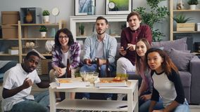 Cheerful guys playing video game while friends watching and laughing at home. Cheerful guys are playing video game holding joysticks while happy friends are stock footage