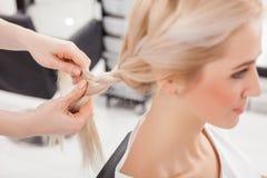 Cheerful hairdresser is braiding human blond hair Stock Photography
