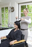 Cheerful hairstylist giving a haircut to beautiful mid adult woman in beauty salon Stock Photos