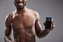 Handsome smiling afro American man holding his cologne royalty free stock photos