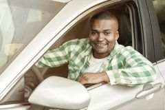Handsome African man choosing new car at dealership royalty free stock photos