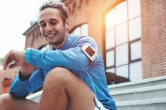Handsome athlete checking time on smart watches after good workout session on the street, sitting on the stairs at sunset stock photos
