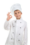 Cheerful handsome boy wearing chef uniform. Portrait of a cute male child cook on white background. Food and cooking concept Stock Photography