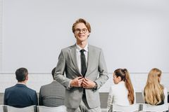 Cheerful handsome coach looking at camera during business training. In hub royalty free stock images