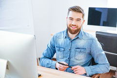 Cheerful handsome designer holding stylus and sitting in office Royalty Free Stock Images